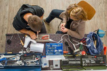 Personen beim Reparieren von alten Sachen